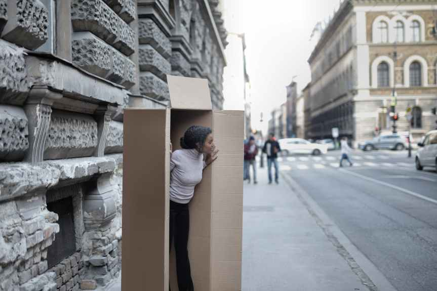 woman peeking out of cardboard box on sidewalk