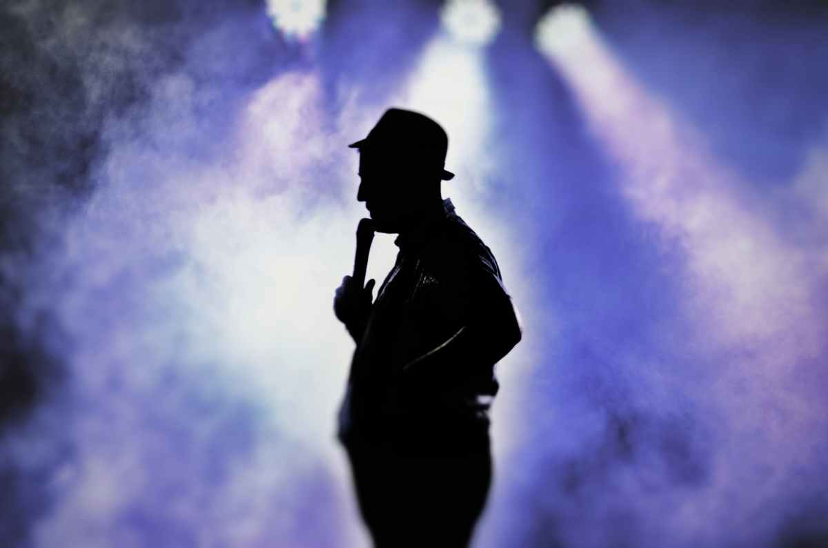 man holding microphone silhouette