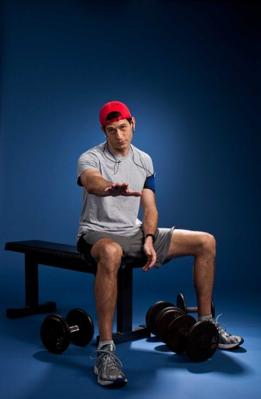 Paul Ryan sitting on a bench, cautioning the viewer. Dumbbells rest on the floor.