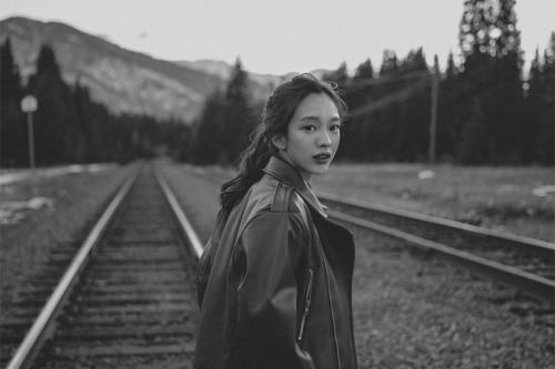 Girl on train tracks looking over her shoulder